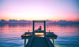 黄昏下在湖边码头坐着的少女摄影图片
