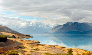 雪山下的湖泊和山路摄影图片