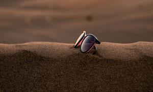 夕阳下放到沙子上的墨镜摄影图片