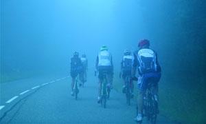 大雾公路上骑行的人群摄影高清图片