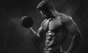 用力握举哑铃的肌肉男摄影高清图片