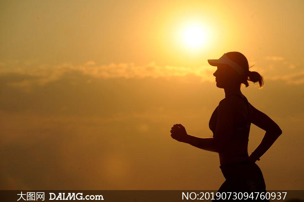 黄昏夕阳下跑步的人物剪影高清图片