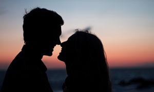 黄昏下情意绵绵的恋人剪影摄影图片