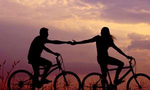 黄昏下的情侣骑车牵手摄影图片