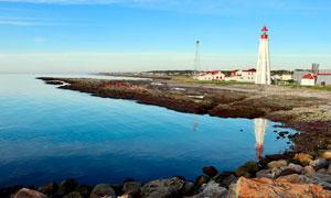 海边灯塔和岩石摄影图片