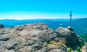 山顶岩石上的十字架摄影图片