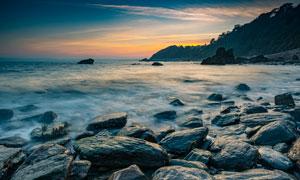 傍晚海边海浪和光滑的石头摄影图片