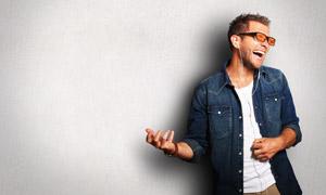 靠着墙壁哈哈笑的男人摄影高清图片