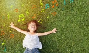 躺草地上的开心小女孩摄影高清图片