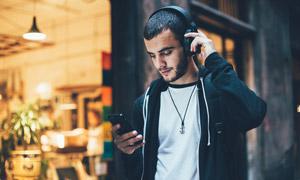 戴着耳机听音?#20540;男?#38386;男子高清图片