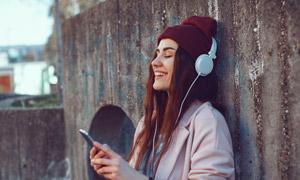 靠墙听音乐的美女人物摄影高清图片