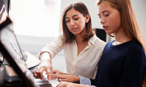 在老師輔導練琴的女孩攝影高清圖片