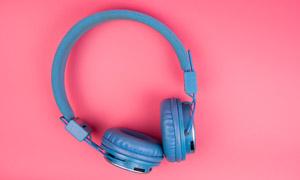 粉色背景上的藍色耳機特寫高清圖片