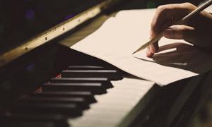 钢琴琴键上写谱子的手特写高清图片