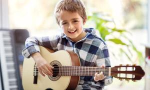 拨动琴弦弹奏吉他的小男孩高清图片