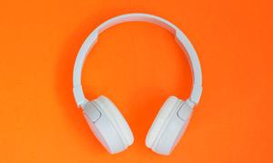 橙色背景上的耳機特寫攝影高清圖片