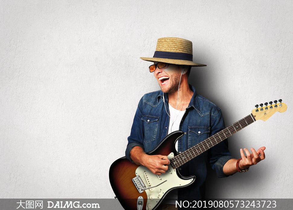 戴着帽子弹吉他的男子摄影高清图片
