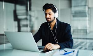 电脑前戴着耳机的男子摄影高清图片
