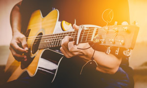 在弹拨吉他试音的人物特写高清图片