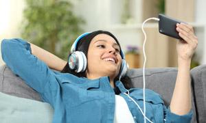 躺沙发听音乐看视频的美女高清图片