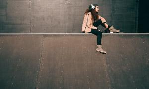 坐在高處聽音樂的女子攝影高清圖片