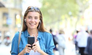 走在街上听音乐的美女摄影高清图片