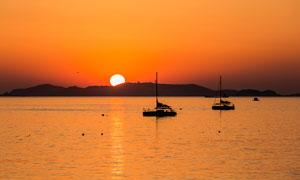 落日下海洋上的渔船摄影图片