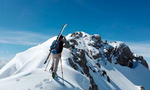 背著雪橇爬雪山滑雪的人攝影圖片