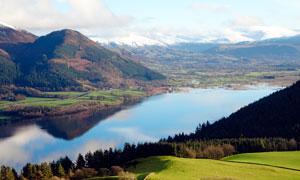 山间湖泊和遥远的雪山摄影图片