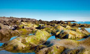 蓝天下的海边岩石景观摄影图片