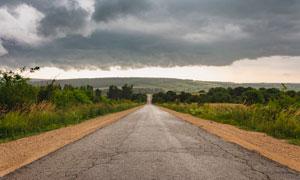 乌云下通往远方的公路摄影图片