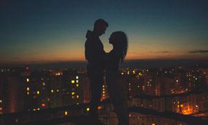 以城市夜景为背景的情侣剪影摄影图片