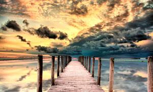 乌云下的湖边木桥摄影图片