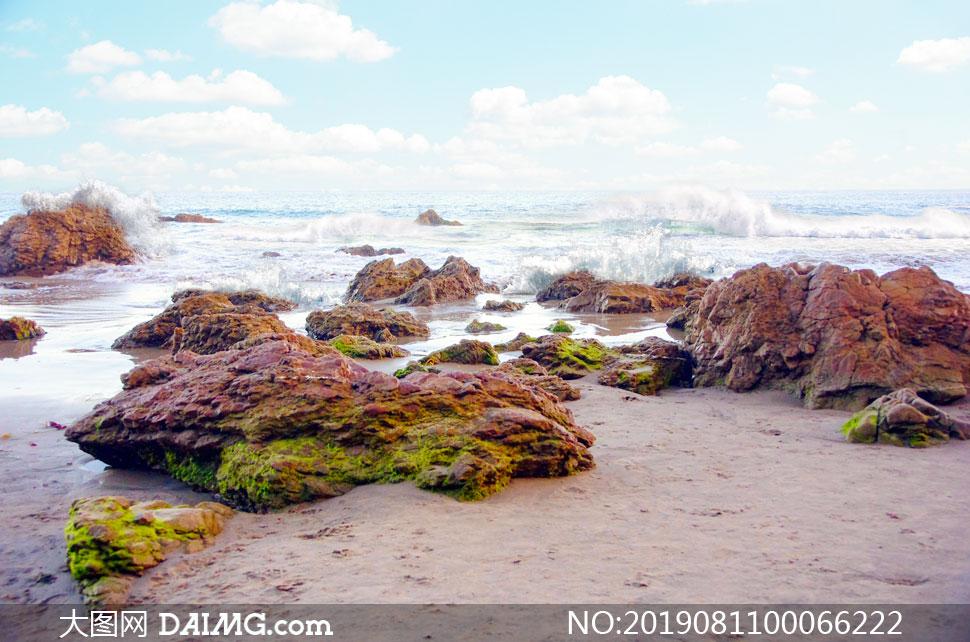 海边浪花击打着岩石摄影图片