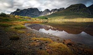乌云下的山中湖泊美景摄影图片
