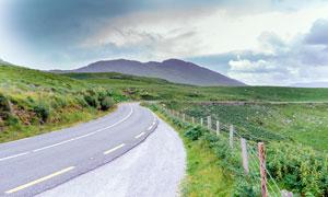 乌云下的弯曲的公路摄影图片