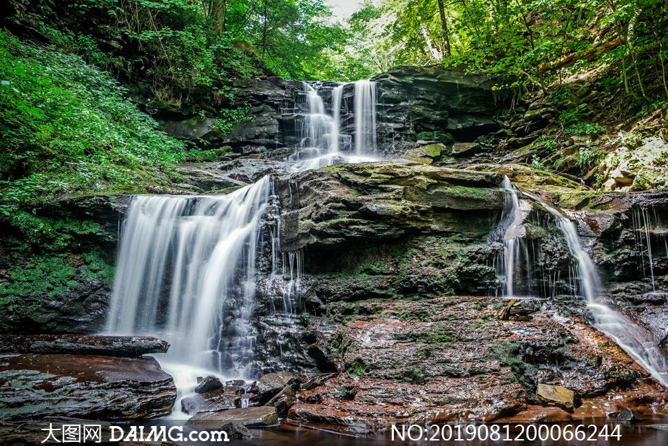 岩层上流下的小溪瀑布摄影图片