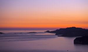 黄昏下的海边礁石和岛屿摄影图片