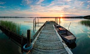夕阳下在湖边木桥停泊的小舟摄影图片