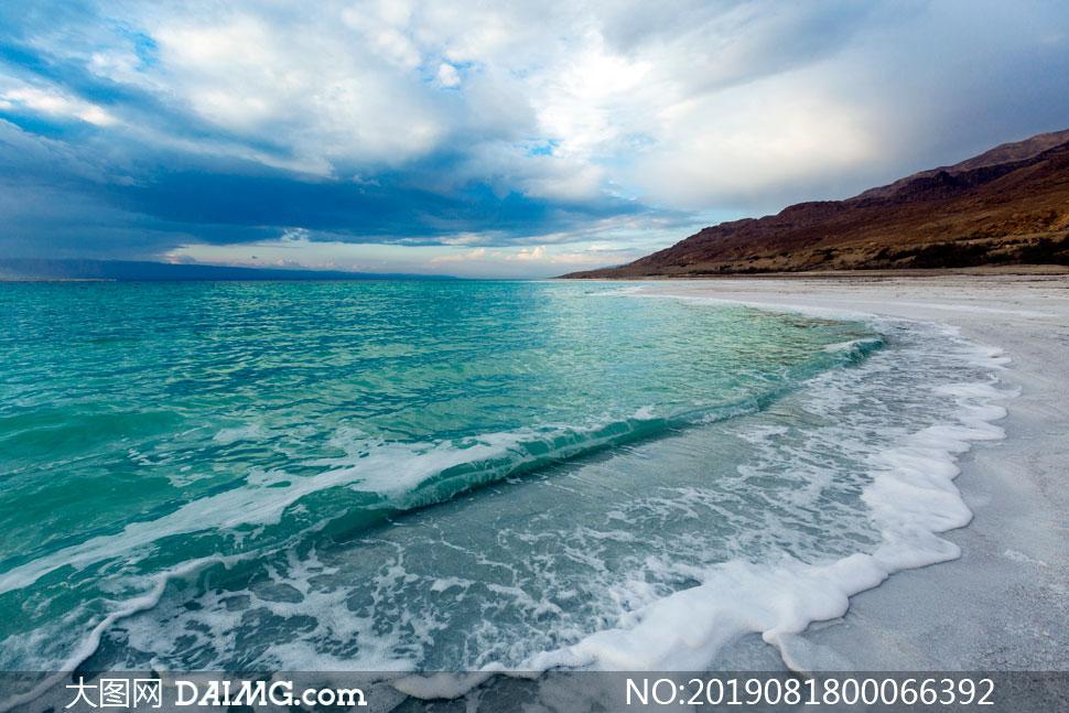 海边沙滩上的海浪摄影图片