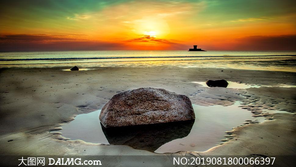 夕阳下海边沙滩上的大石头摄影图片