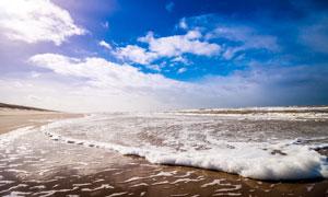 蓝天白云下的海边浪花摄影图片