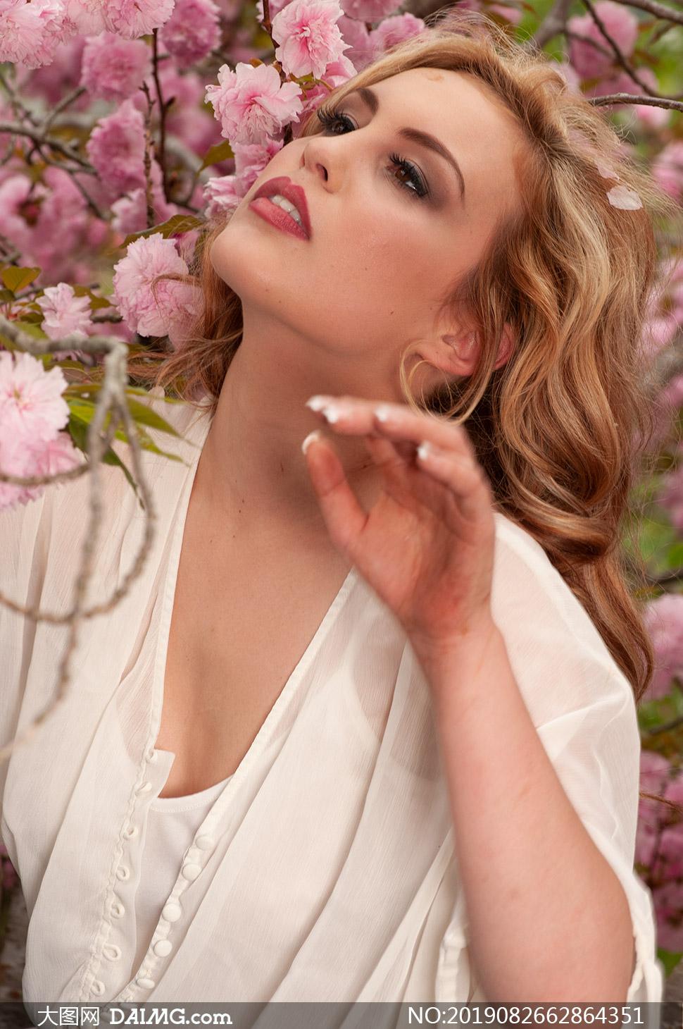 正在闻花香的卷发美女摄影高清图片