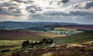 乌云下的山坡和田园景观摄影图片