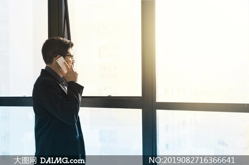 站窗户边打电话的男人摄影高清图片