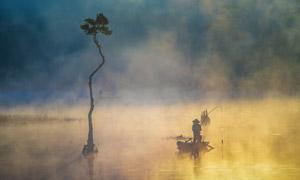 在小木船上钓鱼的人物剪影高清图片