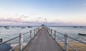 船只与延伸到大海里的栈桥摄影图片