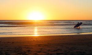 夕阳下在海边冲浪的人摄影图片