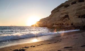 夕阳下海边沙滩和悬崖摄影图片