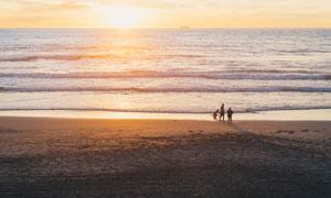 夕阳下的海边沙滩和游人摄影图片